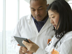Doctors reviewing medical charts, vertical