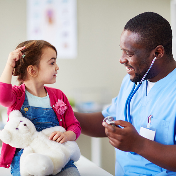 Male doctor caring for preschool-age girl
