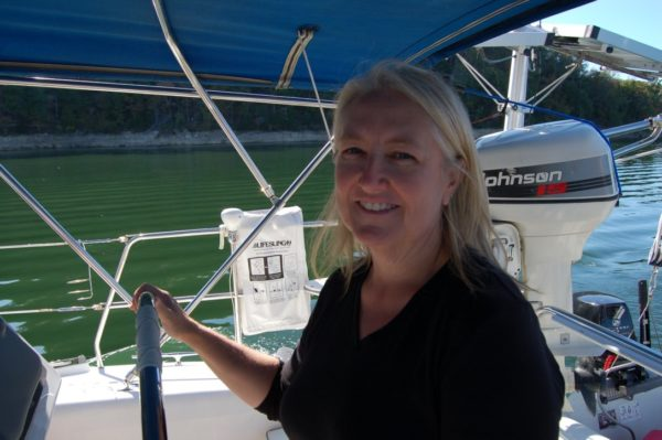 image of locum tenens sailing - doctor robin mangione at the helm of her sailboat