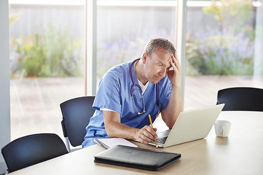 stressed doctor sitting at desk