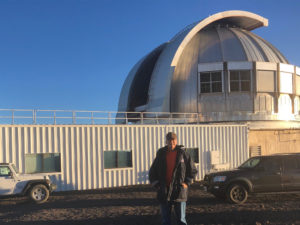 Man standing in front of metal observatory building