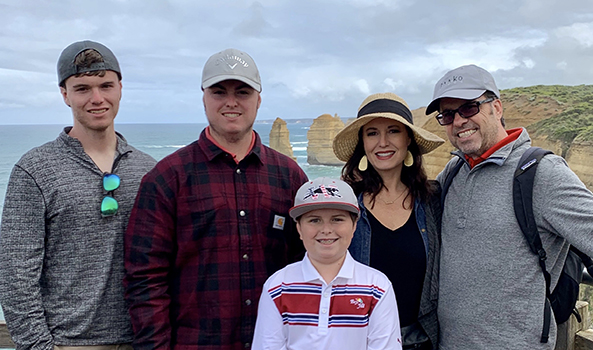 Family of 5 stands in front of ocean