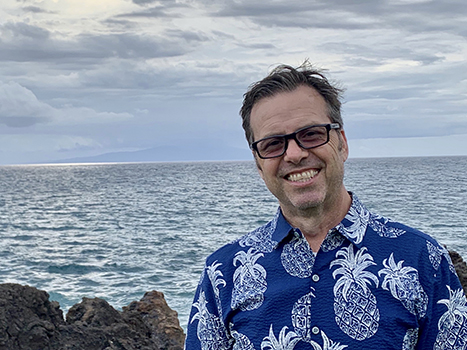 Man stands in front of ocean landscape