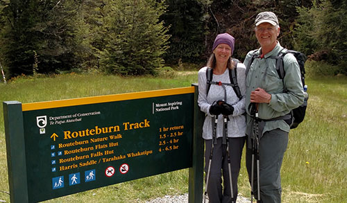Two people stand in front of trail sign