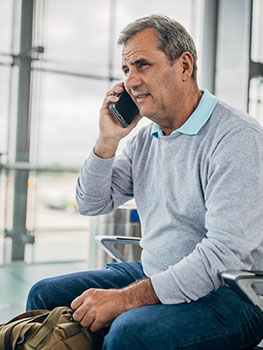 Man sitting inside airport speaking on phone