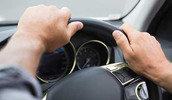 Close up of hands on steering wheel of car - Locum tenens travel tips - drive instead of fly