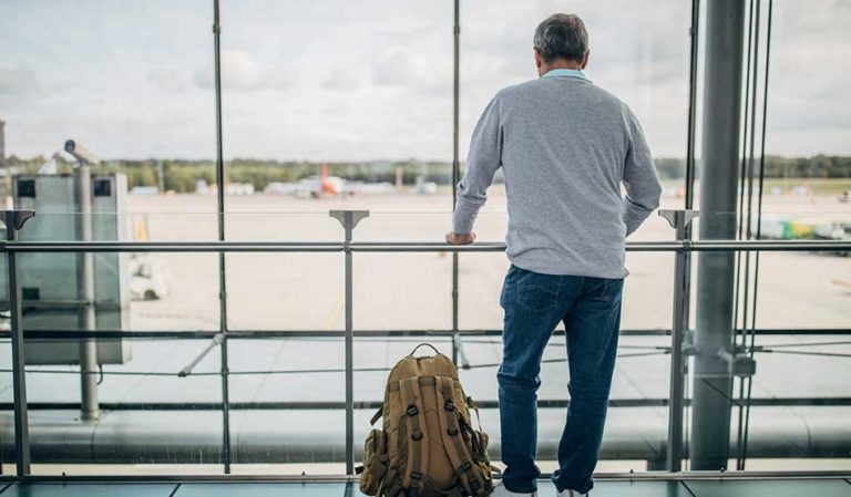 Locum tenens travel tips - Man standing inside airport looking outside of window at airplane