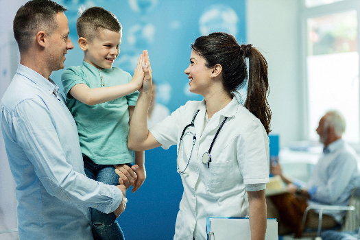 Young doctor giving a child a high five