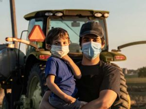 Man and boy wearing masks in front of tractor - covid has affected how rural patients access healthcare
