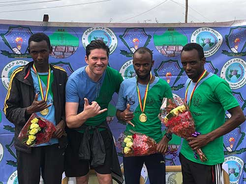 Dr. Barrett with medalist runners in Africa