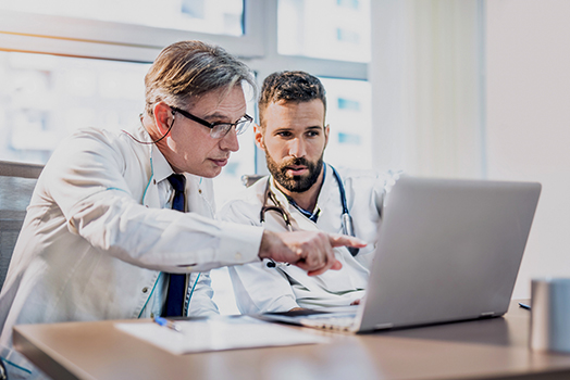 Physician interacting with a colleague at a laptop computer