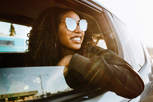 Young locum tenens physician enjoying driving to an assignment